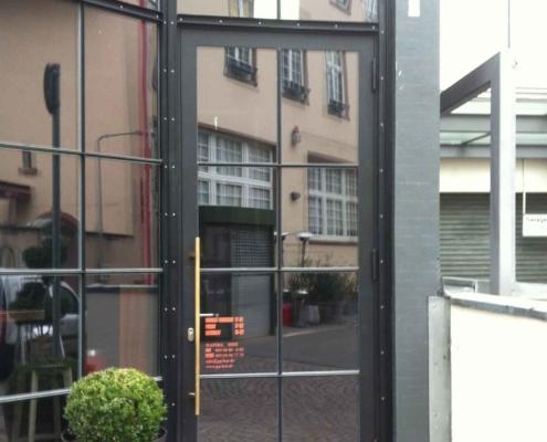 Stahl-Glastür mit Sprossen in einer Stahlfassade