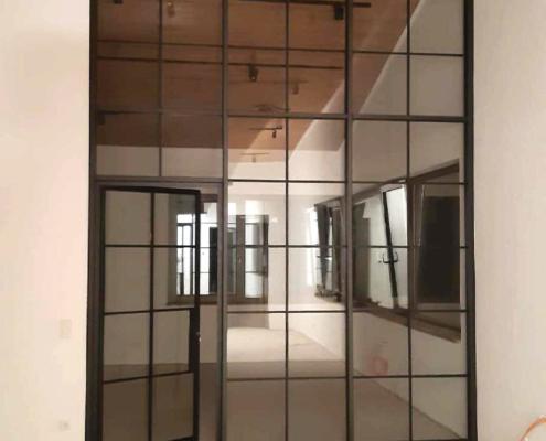 Stahl Glas Trennwand mit Tür im Industriedesign mit Sprossen schwarz